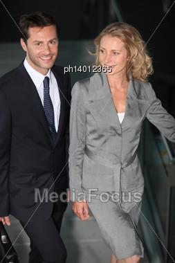 Executive Couple Walking Down A Ramp Stock Photo