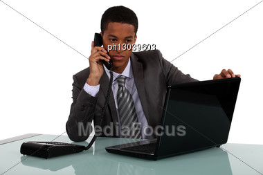Executive With A Phone And Laptop Stock Photo