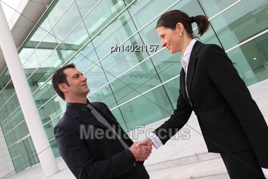 Executives Shaking Hands Outside An Office Building Stock Photo
