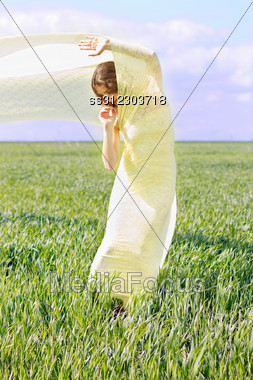 Expressive Young Woman Wrapped In Yellow Cloth Stock Photo