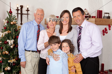 Family With Grandparents On Front Of Christmas Tree Stock Photo