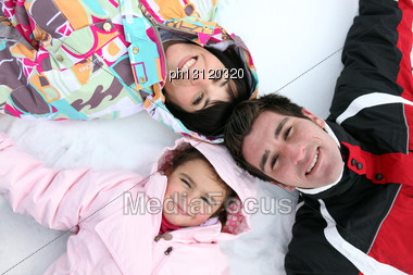 Family Laying In The Snow Stock Photo