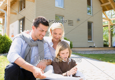 Family Looking At Plans in Front of a House Stock Photo