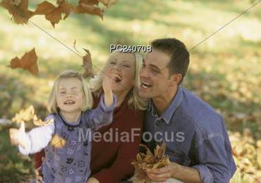 Family Playing with Fall Leafs Stock Photo