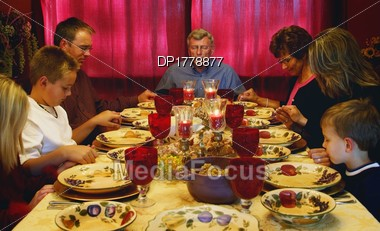 Family Praying Over Thanksgiving Meal Stock Photo