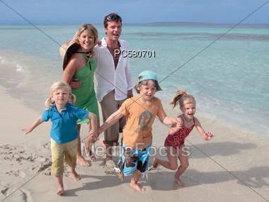 Family & Three Children Walking On The Beach Stock Photo