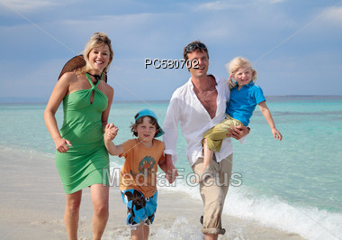 Family with Two Children Walking on the Beach Stock Photo