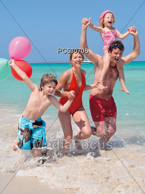 Family With Kids Running On The Beach Stock Photo