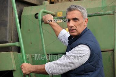 Farmer Climbing Into A Tractor Stock Photo