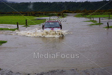 Farmer Crosses A Flooded Creek In His Ute, Westland, New Zealand Stock Photo