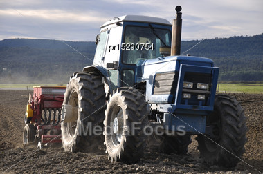 Farmer Drilling Seed Into Pasture Paddock, Westland, New Zealand Stock Photo