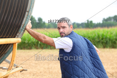 Farmer In A Field With A Reel Of Hose Stock Photo