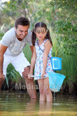 Father And Daughter Fishing In Pond Stock Photo