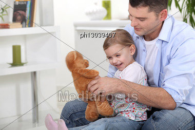 Father And Daughter Playing With Teddy Stock Photo