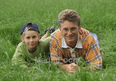 Father and Son Laying in Grass Stock Photo
