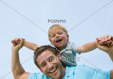 Father With Son On His Back, Laughing Stock Photo