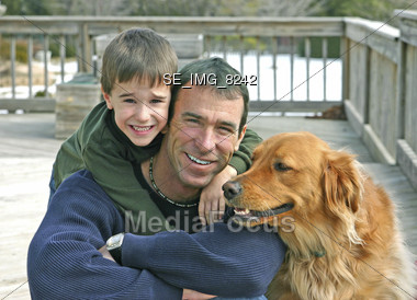 Father and son outside with the family dog Stock Photo