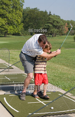 Father Teaching Golf to Son Stock Photo