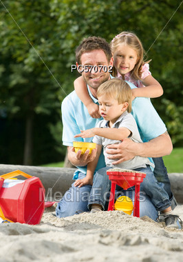 Father With Two Children Playing In Sandbox Stock Photo