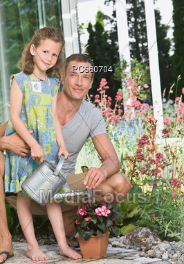 Father with Daughter Watering Flowers Stock Photo
