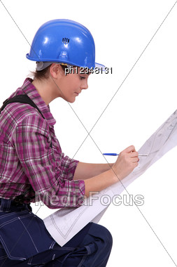 Female Architect In Profile With Blueprints Stock Photo