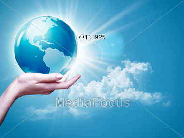 Female Arm Holding Earth Globe Against Blue Skies, Environmental Backgrounds Stock Photo