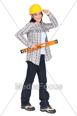 Female Carpenter Holding Ruler With Hand To Hard Hat Stock Photo