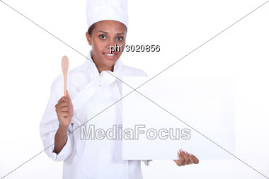 Female Chef Holding Wooden Spoon And Blank Poster Stock Photo