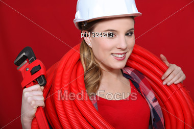 Female Construction Worker Holding Corrugated Tubing And A Pipe Wrench Stock Photo