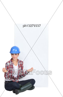 Female Construction Worker In The Lotus Position Stock Photo