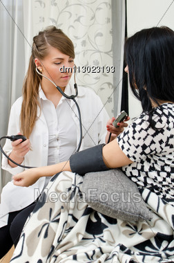 Female Doctor Measures Patient's Blood Pressure Stock Photo