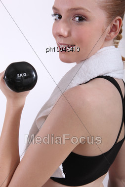 Female Doing Her Workout With A Dumbbell Stock Photo