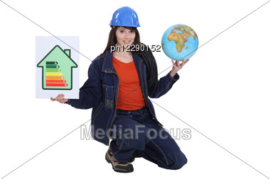 Female Electrician Holding Globe Stock Photo