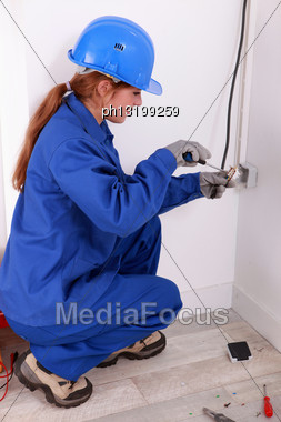 Female Electrician Installing A Wall Socket Stock Photo