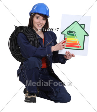 Female Electrician Kneeling Whilst Holding An Energy Rating Poster Stock Photo