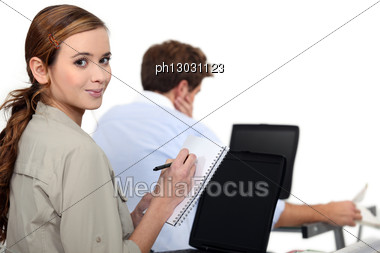 Female Employee Writing Notes Near A Colleague Stock Photo