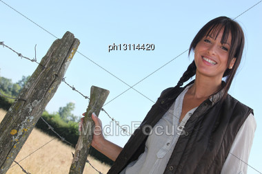 Female Farmer Stood By Barb-wire Stock Photo