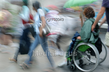 Female Handicapped Person Holding Umbrella On A Wheelchair With Assistant Stock Photo