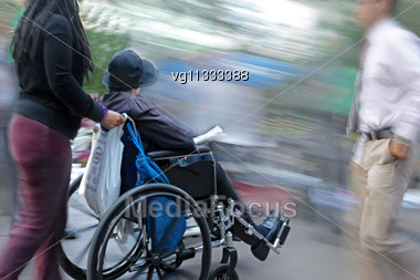 Female Handicapped Person On A Wheelchair With Female Assistant , People Walking By Stock Photo