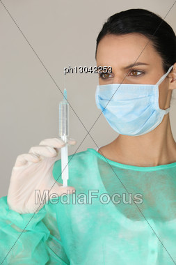 Female Medic Holding A Syringe Stock Photo