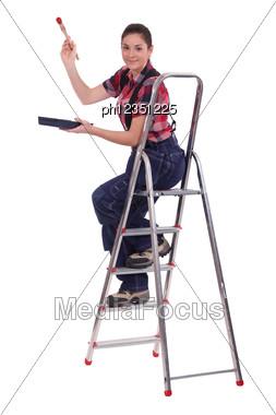 Female Painter On Ladder Stock Photo