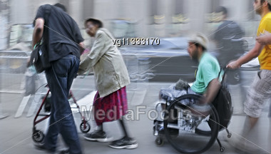 Female Senior Citizen With Walker And Handicapped Person On A Wheelchair Slowly Moving With Assistants N Motion Blur Stock Photo