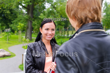 Female Student Chatting With Friend Outdoors Stock Photo