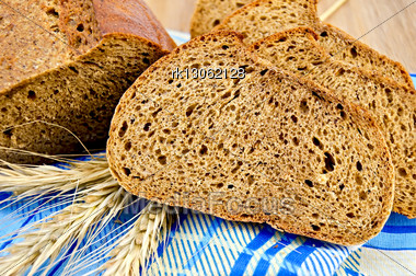 Few Slices Of Rye Bread, Three Rye Spikelets On A Blue Napkin Against A Wooden Board Stock Photo