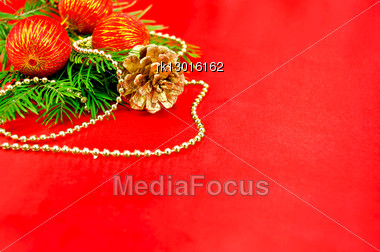 Fir Branches, Three Red Spheres, One Golden Cone, Golden Ornaments Against Red Silk Stock Photo