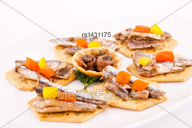 Fish And Peppers On Crackers On White Plate Stock Photo