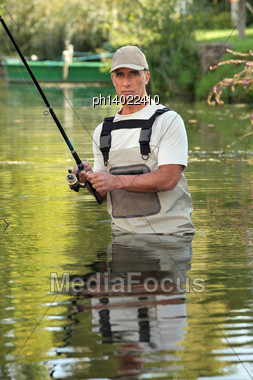 Fisherman In The Water Stock Photo