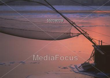 Fishing Net Hanging Over Frozen Lake, Dusk Stock Photo