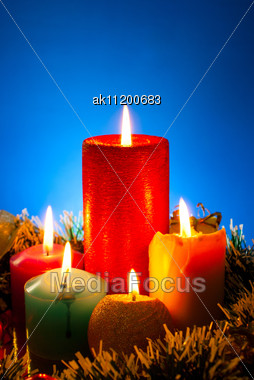 Five Burning Colourful Candles Against Blue Background Stock Photo
