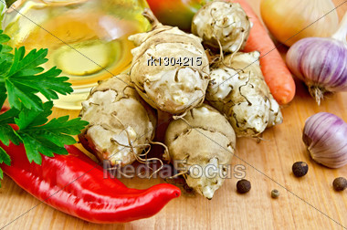 Five Tubers Of Jerusalem Artichoke, Garlic, Onion, Carrot, Parsley, Red Pepper, Peas Sweet Pepper And A Bottle Of Vegetable Oil On A Wooden Board Stock Photo